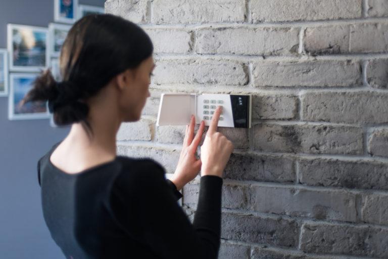 woman setting an alarm system