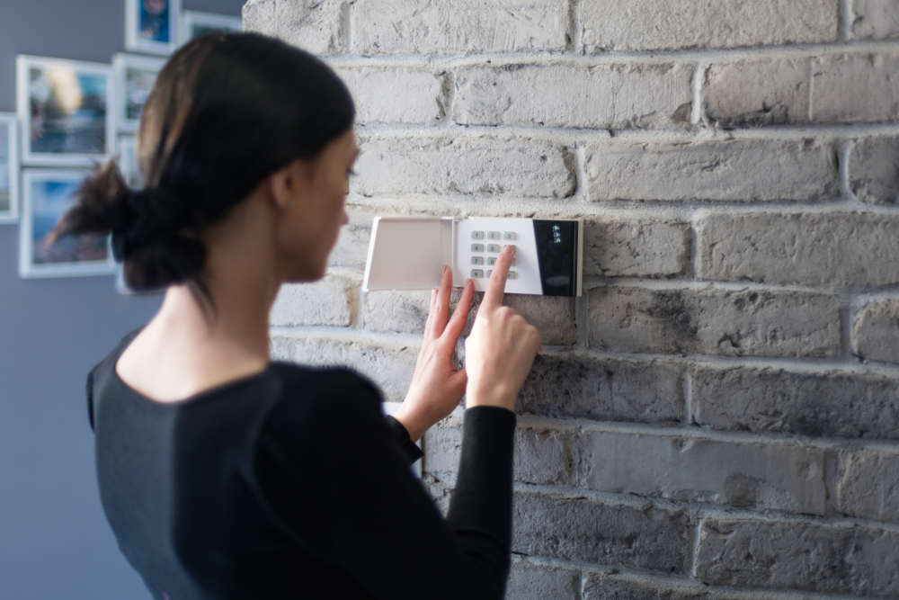 woman setting an alarm system